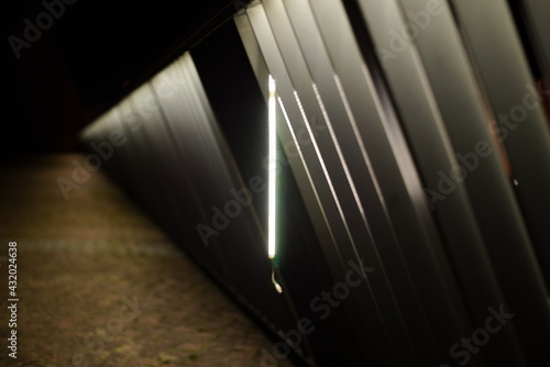 Abstract fence with hanging broken light. - fototapety na wymiar