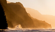 A Wave Crashes Along The Rocky Shores Of Ke'e Beach On Kauai's Na Pali Coastline.