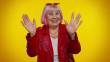Happy Friendly Elderly Granny Woman Waves Hand Palm In Hello Gesture Welcomes Someone With Hospitable Expression Expresses Positive Emotions. Senior Old Grandmother On Yellow Background. Mature Rocker