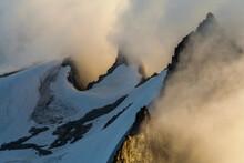 Clouds Surround The Sharp Summit Ridges Of Eldorado Peak At Sunset, North Cascades National Park, Washington.