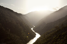 An Unknown River In Kashmir, India With A Sun Setting Over The Mountains In The Background