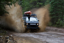 A Volkswagen Synchro Van Charges Through A Mud Puddle On A Dirt Back Road.