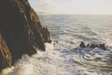 Waves Crash Against The Base Of A Cliff On The Oregon Coast.