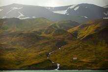 A Glacial Waterfall And Abandoned Homestead On The Coast Of Skjalfandi Bay, Near Husavik, In Northern Iceland.