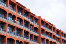 Balconies On Facade Of Red Painted Apartment Blocks