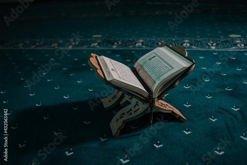 Fototapeta Closeup of an opened holy book of Quran put on a wooden pedestal on a carpet