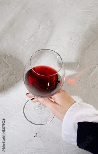 Obraz Young woman holding glass of red wine on white background. Hand with black polish. - fototapety do salonu
