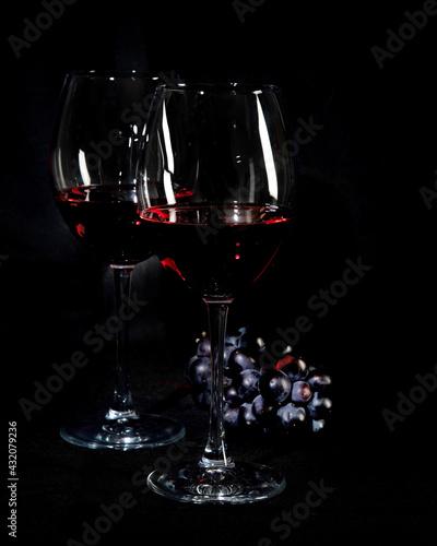 Obraz Red wine bottle with 2 glasses and bottle opener on black background. - fototapety do salonu