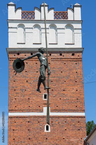Fotografie, Obraz 14th century gothic entrance Opatowska Gate, sculpture of a bargeman going down