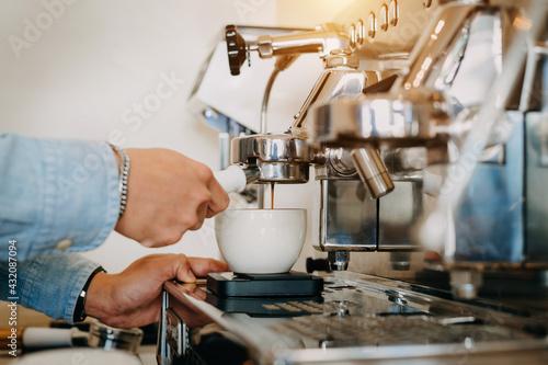 Obraz Closeup Professional coffee brewing. Side view of espresso pouring into ceramic cups - fototapety do salonu