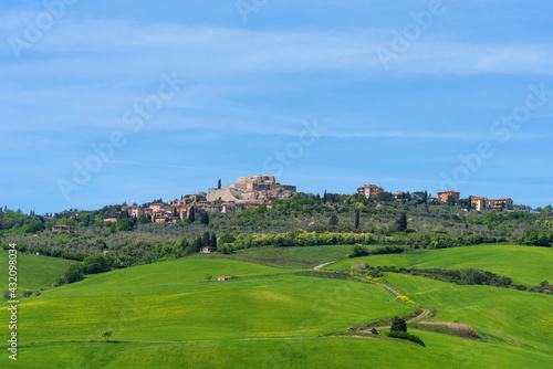 Fototapeta premium Panoramic landscape of the Italian Tuscan town with stone houses, a fortress on the mountain and green fields in spring.