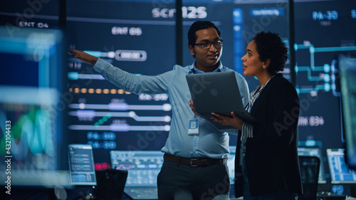 In the System Control Room Project Manager and IT Technical Engineer with Laptop Have Discussion, surrounded by Multiple Monitors with Graphics. Big Monitor Shows Interactive Server Blockchain Info. - fototapety na wymiar