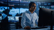 Leinwandbild Motiv Portrait of Professional IT Technical Support Specialist Working on Computer in Monitoring Control Room with Digital Screens. Employee Wears Headphones with Mic and Talking on a Call.