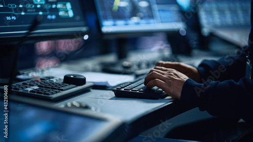 Close Up of a Professional Office Specialist Working on Desktop Computer in Modern Technological Monitoring Control Room with Digital Screens. Manager Typing on keyboard and Using Mouse. - fototapety na wymiar