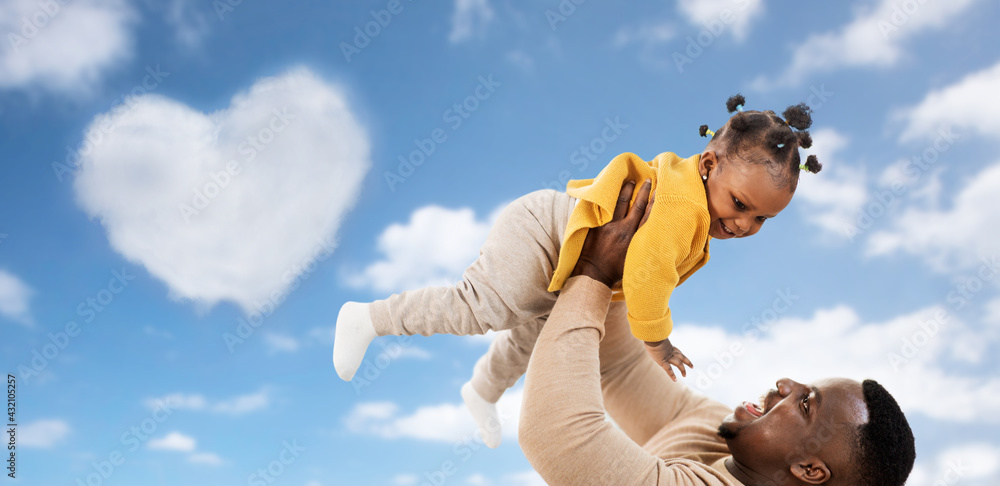 Leinwandbild Motiv - Syda Productions : family, fatherhood and people concept - happy african american father playing with baby daughter over blue sky and clouds background