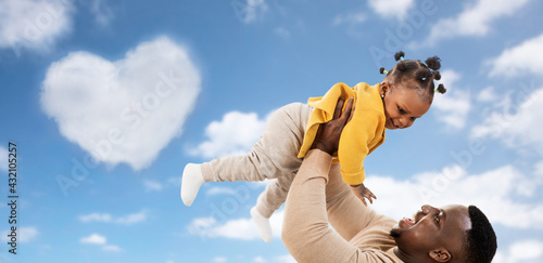 family, fatherhood and people concept - happy african american father playing with baby daughter over blue sky and clouds background