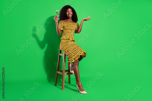 Obraz Full size photo of attractive black woman happy positive smile sit bar drink champagne isolated over green color background - fototapety do salonu