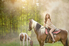 Barefoot Woman Riding A Horse In A Meadow, Thailand