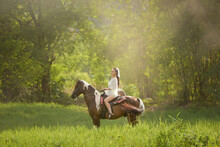 Beautiful Woman Riding A Horse In A Meadow, Thailand