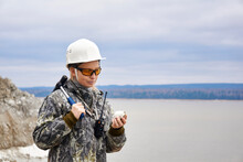 Woman Geologist Examines A Mineral Sample At The Edge Of The Quarry