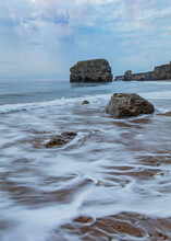 Marsden Rock. South Shields, England, In Early Morning Light. With Waves Washing Over The Beach And Rocks.