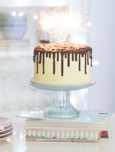 Vanilla Birthday Cake With Chocolate Ganache, Glaze, And Sparklers On A Cake Stand In A  Kitchen