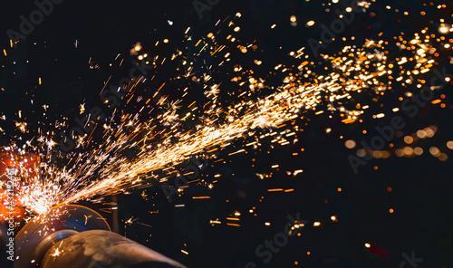 Fototapeta Hot sparks at grinding steel material  obraz