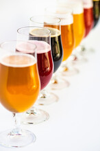 A Row Of Assorted Craft Beers Lined Up On A Table