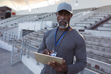 Portrait Of African American Male Coach Holding Clipboard Standing In The Stadium