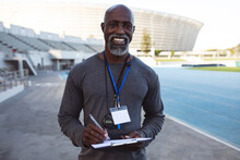 Portrait Of African American Male Coach Holding Clipboard Smiling While Standing In The Stadium