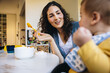 Leinwandbild Motiv Caring mother feeding toddler while on maternity leave
