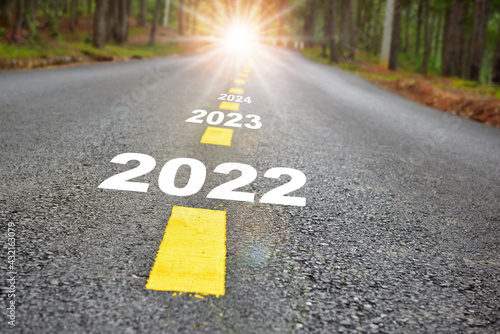 Fototapeta 2022 to 2024 road to recovery with sunbeam. Challenge with success concept and natural background idea obraz