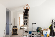 Female Electrician Renovating House