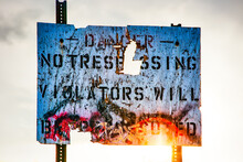 Battered Distressed Danger No Trespassing Sign. With Sun Directly In Back. Isolated.