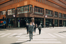 Business People Crossing Street On Sunny Day During COVID-19