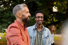 Smiling Male Friends Talking In Park