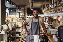 Portrait Of Smiling Male Owner With Hand On Hip Standing In Delicatessen Shop