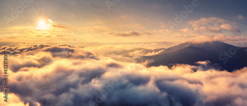 Fototapeta Aerial view of mountains in orange clouds at sunrise in summer. Mountain peak in fog. Beautiful landscape with rocks, hills, sky. Top view from drone. Mountain valley in low clouds. View from above obraz