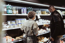 Male Customer Picking Up Food Product Standing By Female Owner In Store During COVID-19