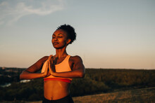 Young Sportswoman Meditating Against Sky During Sunset