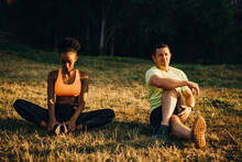 Sportsman And Sportswoman Doing Relaxation Exercise While Sitting On Grassy Area