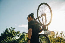 Male Athlete Carrying Bicycle On Shoulder Against Sky On Sunny Day