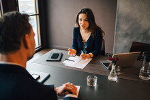 Businesswoman Discussing With Male Colleagues At Conference Table In Office