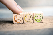 Bad Feedback Concept With Red, Yellow And Green Smiling Faces On Wooden Blocks On A Board, The Red Face Is Touched By A Finger