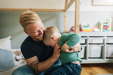 Smiling Father Tickling Son While Sitting In Bedroom