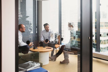 Male Entrepreneurs Planning Strategy During Meeting Seen Through Door Office