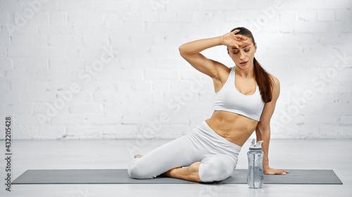 Obraz Tired woman sitting on yoga mat near sport bottle. - fototapety do salonu