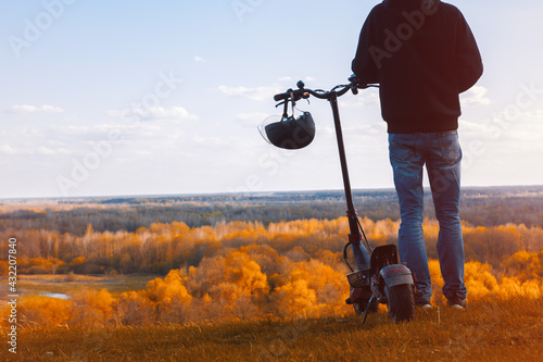 A young man on an electric scooter on the observation deck admires the autumn landscape Wallpaper Mural