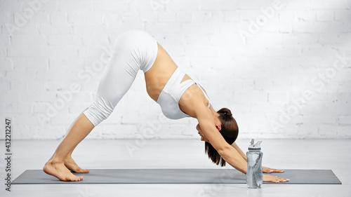 Obraz Side view of woman standing in downward-facing dog pose near sports bottle. - fototapety do salonu