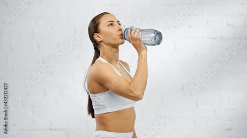 Obraz Sportswoman drinking water from sports bottle at home. - fototapety do salonu